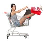 俏丽的深色的妇女在有s的一辆空的购物台车坐 库存照片