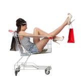 俏丽的深色的妇女在有s的一辆空的购物台车坐 免版税库存图片