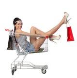 俏丽的深色的妇女在有s的一辆空的购物台车坐 库存图片