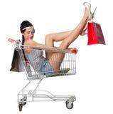 俏丽的深色的妇女在有s的一辆空的购物台车坐 免版税库存照片