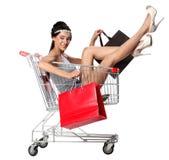 俏丽的深色的妇女在有s的一辆空的购物台车坐 免版税图库摄影
