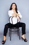 俏丽的深色的确信的成熟妇女坐在studi的椅子 免版税库存图片