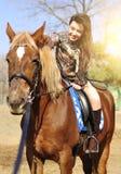 年轻俏丽的深色的骑马和爱抚室外她的马 免版税库存图片