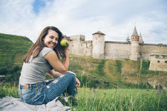 俏丽的游人坐在老城堡前面的岩石并且吃aplle 库存图片
