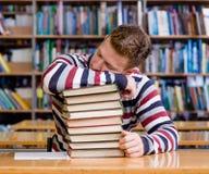 俏丽的男学生睡眠在图书馆里 免版税库存图片