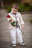 俏丽的男孩举行红色玫瑰在手中 库存图片