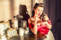 俏丽的画报女孩吃在减速火箭的内部的蛋糕 免版税库存照片