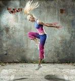 俏丽的白肤金发的妇女跳舞在一个脏的地方 库存图片