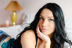 俏丽的看照相机的绿松石丝绸衬衣的迷人的美丽的少妇说谎在白色床背景特写镜头画象 免版税图库摄影
