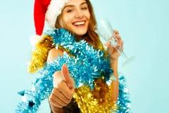 俏丽的礼服的年轻可爱的圣诞老人女孩在蓝色背景 免版税图库摄影