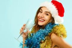 俏丽的礼服的年轻可爱的圣诞老人女孩在蓝色背景 免版税库存图片