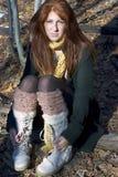 俏丽的红头发人坐的森林 免版税库存照片