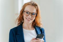 俏丽的红头发人女性directror接近的射击有迷人的微笑,穿戴在典雅的衣裳,拿着手机,检查文本 免版税图库摄影