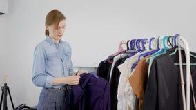 俏丽的红头发人妇女在家观看在挂衣架的蓝色礼服,离开它,排序单独她的衣橱 股票视频