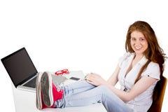 俏丽的红头发人的综合图象与脚的在书桌上 库存照片