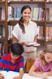 俏丽的老师帮助的学生在图书馆里 免版税库存照片