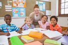 俏丽的老师帮助的学生在教室 免版税库存照片