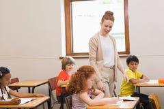俏丽的老师帮助的学生在教室 库存图片