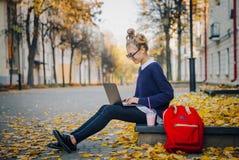 俏丽的行家青少年的女孩坐在秋天城市街道和运转的便携式计算机上的一条边路 女小学生使用 免版税图库摄影
