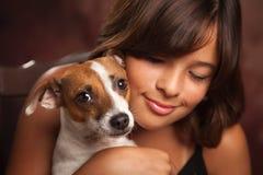 俏丽的西班牙女孩和她的小狗演播室画象 库存照片