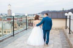 俏丽的走在大阳台的新娘和深色的新郎有都市风景背景 图库摄影