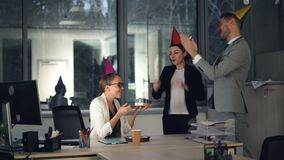 俏丽的金发碧眼的女人在现代办公室,当她的同事带来生日蛋糕、礼物和党帽子时,女孩工作 影视素材