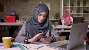 俏丽的阿拉伯女性猛击她的智能手机,工作环境,交换在膝上型计算机,背景的ar回教女孩 影视素材