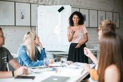 俏丽的非裔美国人的女孩站立近的委员会和愉快地谈论新的项目与同事在办公室 22个项目符号口径组白色 免版税库存照片