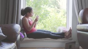 俏丽的非裔美国人的妇女坐与指甲锉的窗口基石切制钉 关心对她自己的女孩 股票视频
