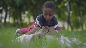 俏丽的非裔美国人的妇女说谎在草的在公园,她的坐在她顶部的小儿子接触她的面孔 影视素材