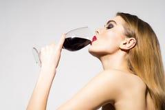 俏丽的魅力女孩饮用的酒 免版税图库摄影
