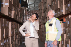 俏丽的仓库经理谈话与工头 免版税库存图片