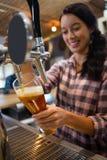 俏丽的从轻拍的女服务员倾吐的啤酒在玻璃 库存照片