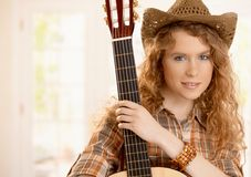 俏丽的guitarplayer女孩拥抱吉他 免版税库存图片