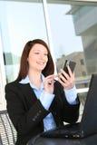 俏丽的texting的妇女工作 免版税库存图片