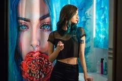 俏丽,在她的卫生间镜子前面的少妇胭脂红色唇膏 头发电烫 有艺术绘画的淋浴帘 免版税图库摄影