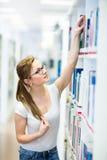 俏丽,女性大学生在图书馆里,寻找书 库存照片