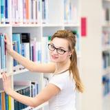 俏丽,女性大学生在图书馆里,寻找书 免版税图库摄影