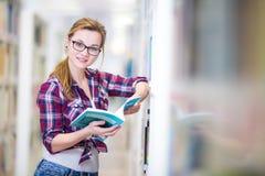 俏丽,女性大学生在图书馆里,寻找书 库存图片