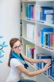 俏丽,女性大学生在图书馆里 免版税图库摄影