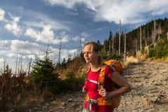 去俏丽,女性的远足者下坡 免版税图库摄影