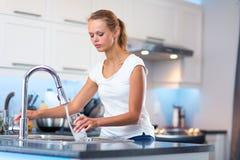 俏丽,少妇在她的现代厨房里 图库摄影
