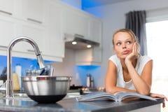 俏丽,少妇在她的现代,干净和明亮的厨房里 免版税图库摄影