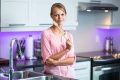 俏丽,少妇在她的现代,干净和明亮的厨房里 库存照片