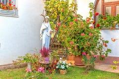 保佑的圣母玛丽亚的雕象在庭院里 免版税库存照片