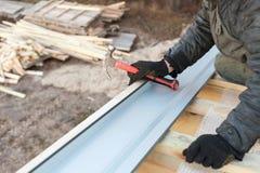 保养概念 成人职业人室外照片有手设备锤子的建立联系在未完成的屋顶小 库存图片