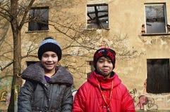 保加利亚女孩和一个吉普赛男孩在被破坏的老居民住房前面一起使用 免版税库存图片