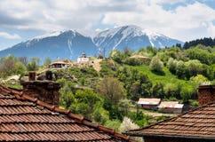 保加利亚山村、小教堂和雪山 免版税图库摄影