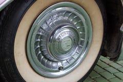 保加利亚,埃尔霍沃- 2017年10月07日:桃红色卡迪拉克系列62小轿车1958徽章 桃红色卡迪拉克汽车轮子细节  库存图片