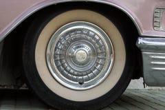 保加利亚,埃尔霍沃- 2017年10月07日:桃红色卡迪拉克系列62小轿车1958徽章 桃红色卡迪拉克汽车轮子细节  免版税库存图片